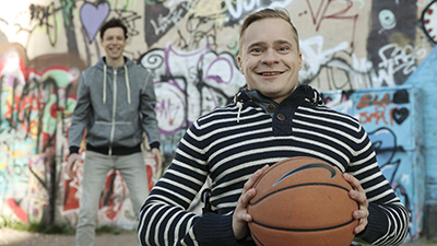 Two men outdoors playing basketball