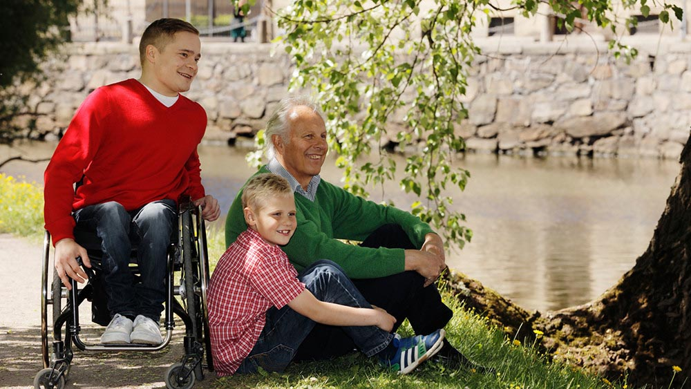 Wellspect Lofric Man in wheelchair joining an older man with granddaughter in the park by the pond